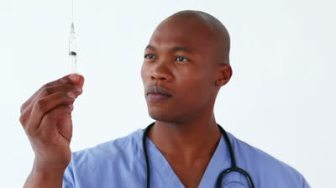 stock-footage-happy-doctor-preparing-a-syringe-against-a-white-background